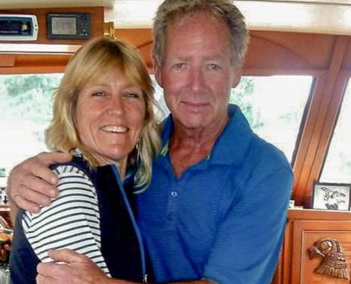 Toddy & Alan Landry, owner operator couple & tour hosts, standing inside saloon of their boat