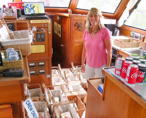 Toddy standing inside boat beside a dozen picnic baskets containing gourmet lunches