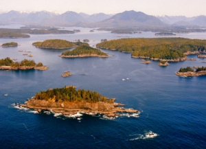Aerial view over Broken Group Islands - islands, ocean, snow capped mountains in the distance