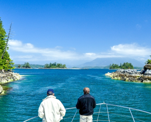 Broken Group Islands - two men standing on bow of boat as it approaches a narrow channel between two islands