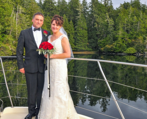 Groom and bride in traditional dress & holding red roses, on bow of boat anchored in calm location