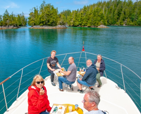 six guests sitting at tables on bow of boat, having lunch. Calm, blue ocean and islands in background