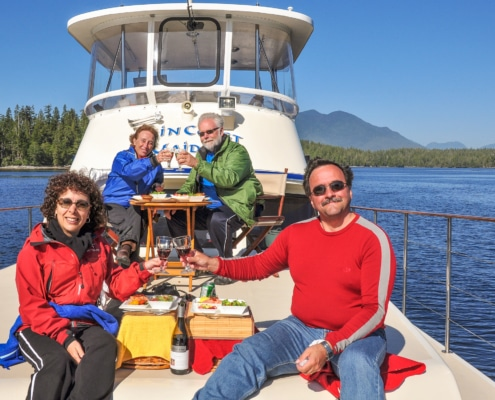 Four guests sitting in sun on the bow of boat having gourmet meal.