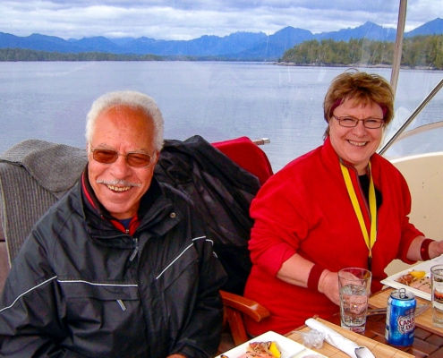 Two guests sitting at table under cover on upper deck of boat , having lunch