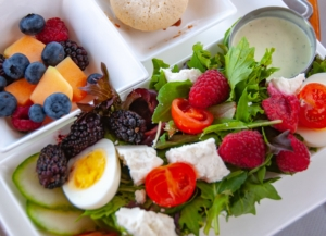 Cobb salad, greens with egg, feta cheese and berries, portion of mixed fruits & berries, macaron