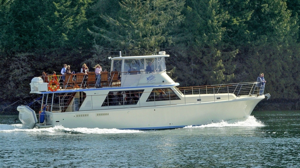 Side view of spacious 53 foot luxury motor yacht, underway, with a group of passengers aboard