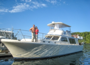 Luxury motor yacht, front ad side view, owners standing on bow