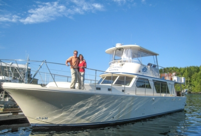 Luxury motor yacht, front and side view, owners standing on bow