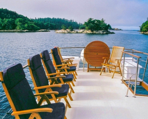 Upper deck of motor yacht, showing several deck chairs with navy blue seat cushions, ocean & island in background