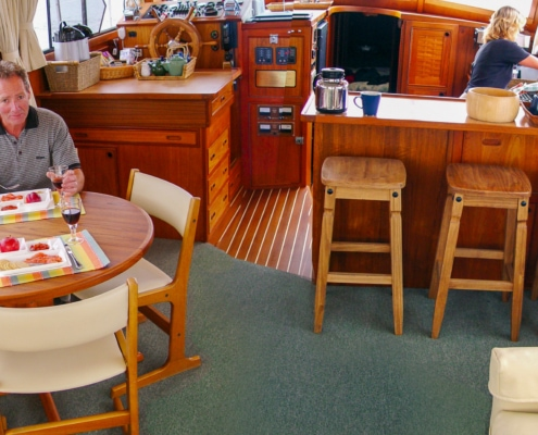 Inside luxurious saloon of motor yacht, showing bar counter, man sitting at dining table, lady in galley