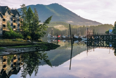 Calm waters in Ucluelet harbour. Resort on left side of image and fishing boats tied up in marina in background.