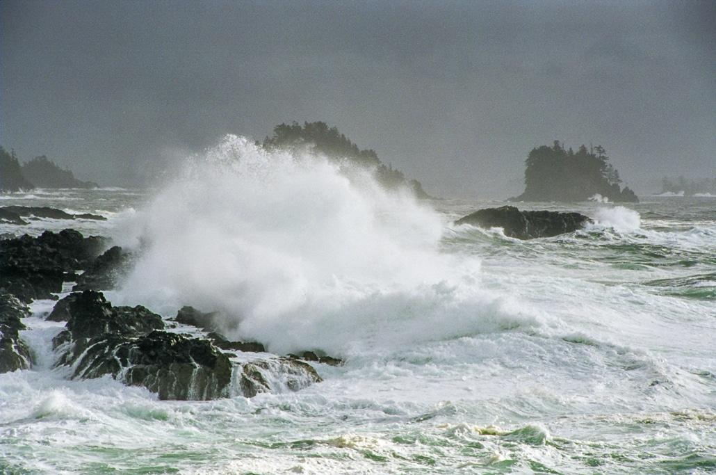 Waves crashing over black rocks on stormy day